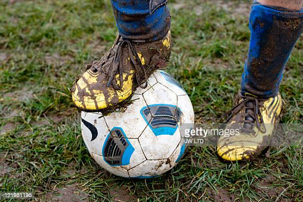 Close up of muddy football boot on football