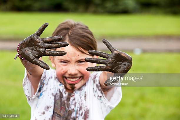 Close up of muddy hands on girl