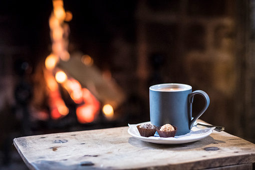 Close up of mug with hot drink on wooden table in front of fireplace. - gettyimageskorea