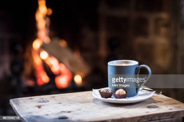 close up of mug with hot drink on wooden table in front of fireplace. - camino foto e immagini stock