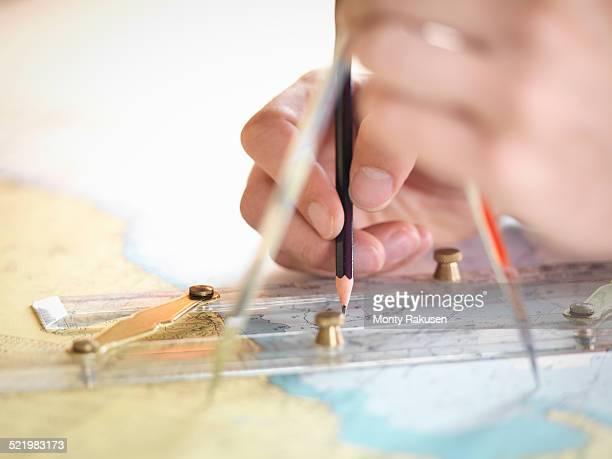 Close up of navigator checking charts on ships bridge