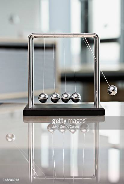 close up of newton's cradle on table - desk toy stock photos and pictures