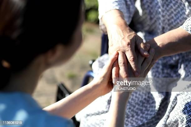 close up of nurse holding senior man's hands - aide soignante photos et images de collection