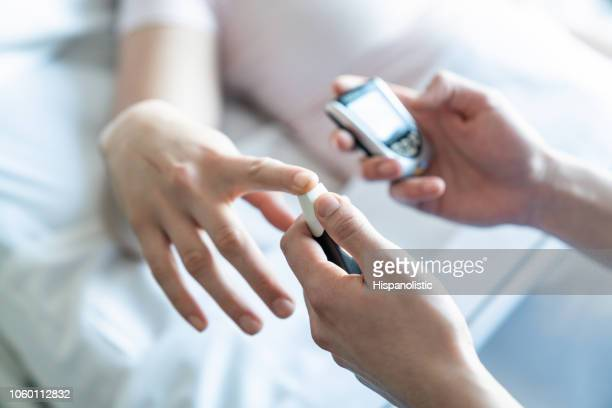 close up of nurse pinching patients finger to measure sugar level with a glucometer - glycemia stock pictures, royalty-free photos & images