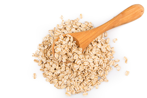 close up of oatmeal flakes in wooden spoon on white background - gettyimageskorea