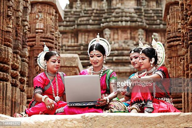 Close up of odissi dancers working on laptop