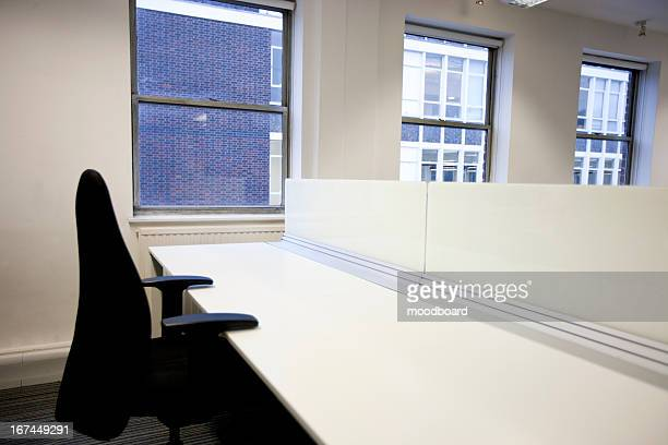 close up of office chair and empty desk by window - empty desk stock pictures, royalty-free photos & images