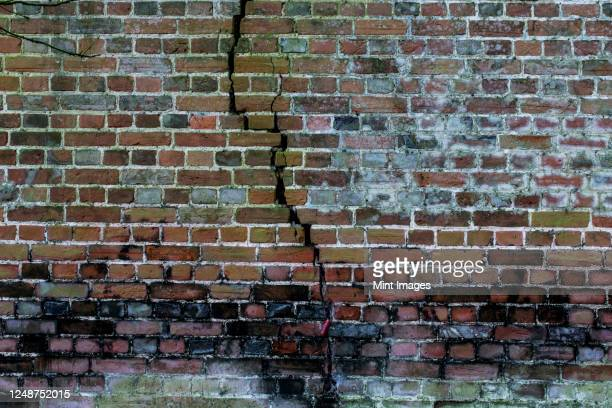 close up of old and cracked brick wall overgrown with moss. - brick wall stock pictures, royalty-free photos & images