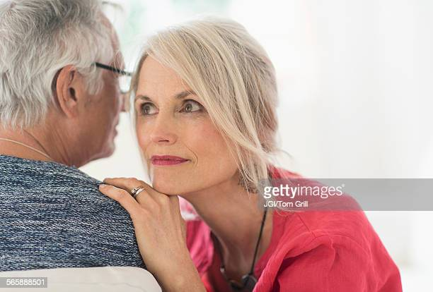 Close up of older Caucasian couple whispering