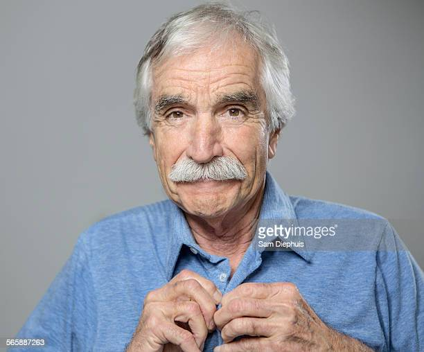 Close up of older Caucasian man buttoning his shirt