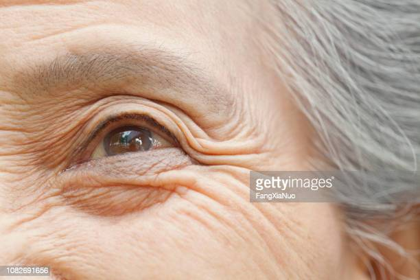close up of older chinese woman's eye - extreme close up stock pictures, royalty-free photos & images
