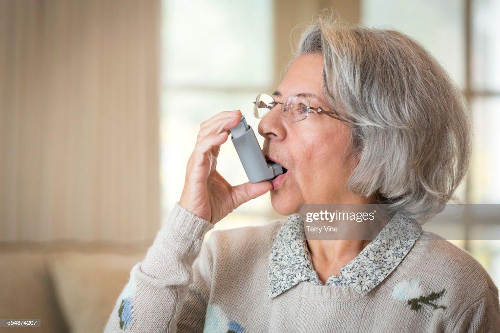 Close up of older Hispanic woman using asthma inhaler : Stock Photo
