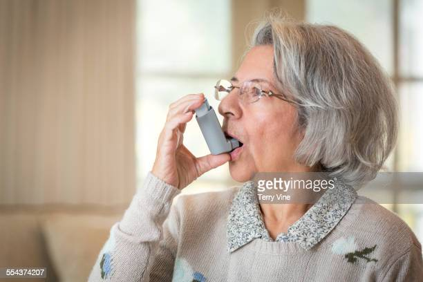 close up of older hispanic woman using asthma inhaler - asthmatic stock photos and pictures