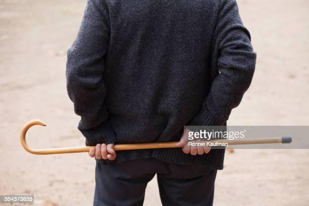 Close up of older man holding cane behind his back