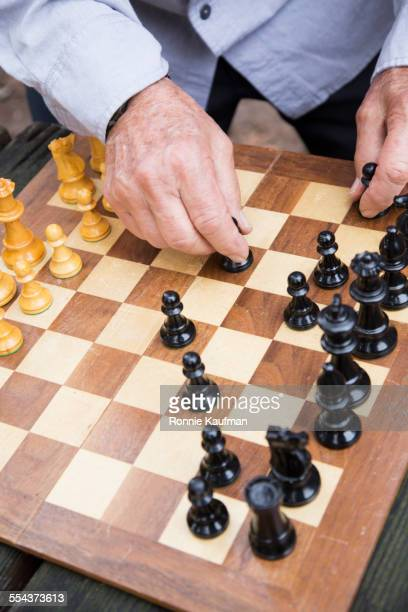Close up of older man playing chess in park