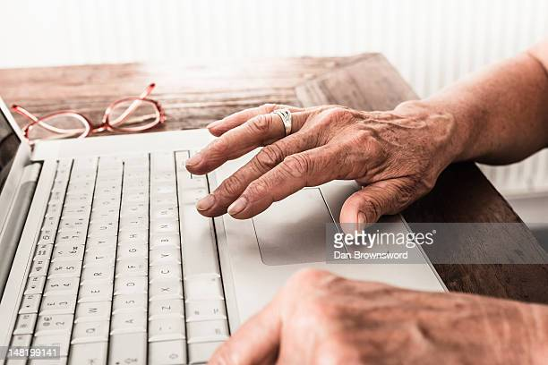 Close up of older mans hands on laptop