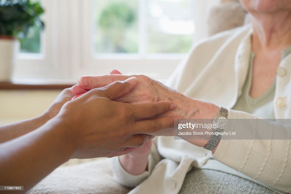 Close up of older woman and caretaker holding hands : Stock Photo