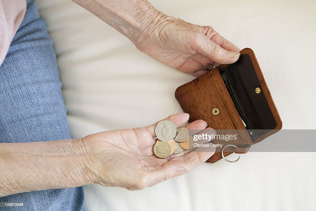 Close up of older woman counting coins : Stock Photo