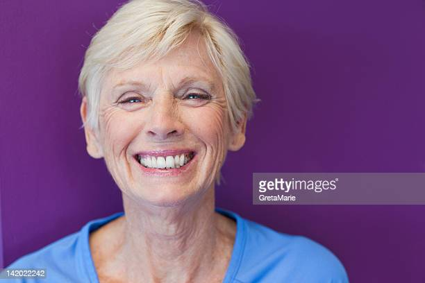 close up of older womans smiling face - purple background stock photos and pictures