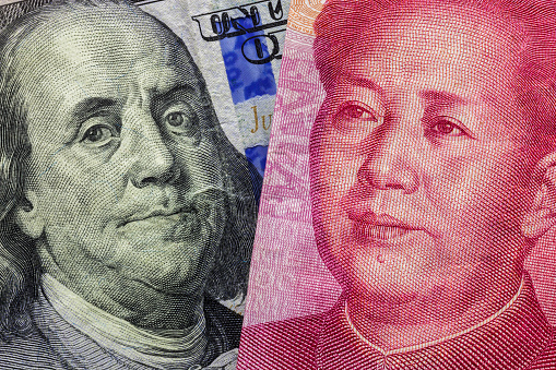 Close up of one hundred Dollar and 100 Yaun banknotes with focus on portraits of Benjamin Franklin and Mao Tse-tung/USA vs China trade war concept 941940090