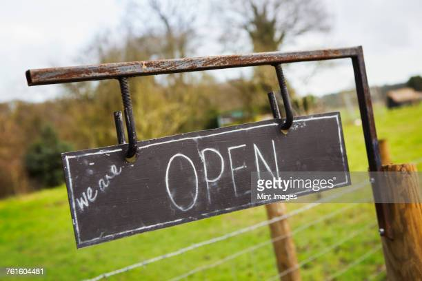 close up of open sign on a fence at a farm shop. - road sign board stock pictures, royalty-free photos & images