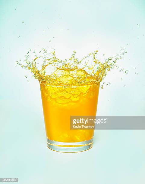 Close up of orange juice splashing out of glass