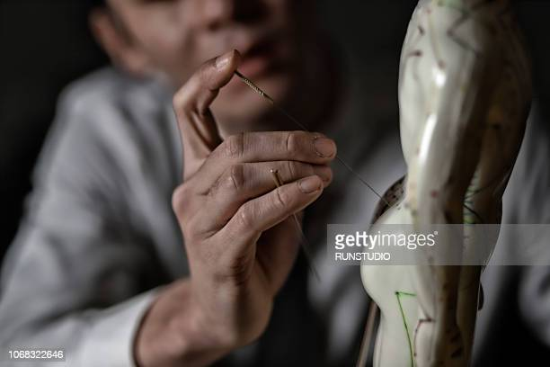 Close up of oriental medical doctor applying needles on acupuncture model
