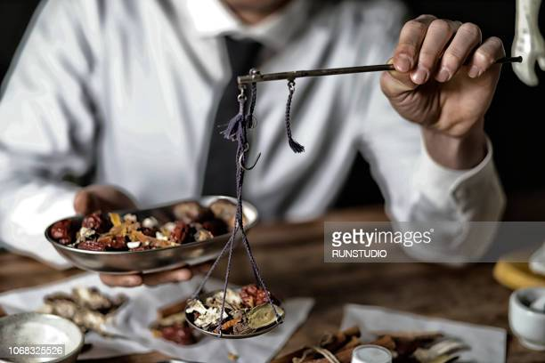 Close up of oriental medicine doctor weighing herbal medicines with scales