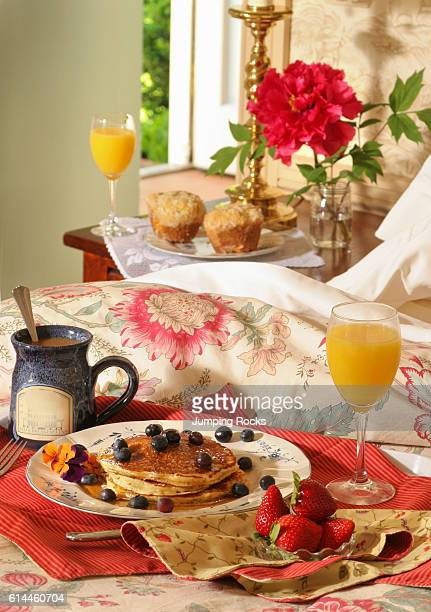 Close up of pancakes and fruit with glass of orange juice