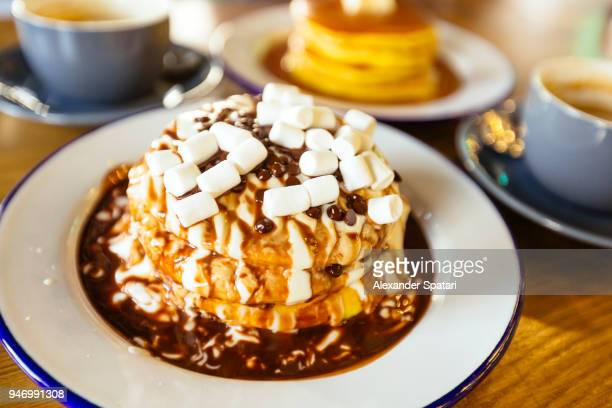 Close up of pancakes with chocolate, caramel and marshmallow toppings on the table