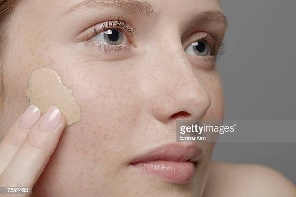 Close up of part of young woman's face, applying concealer