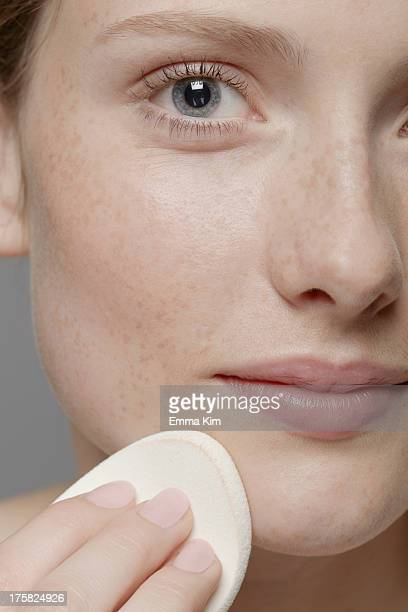 Close up of part of young woman's face, cleansing face