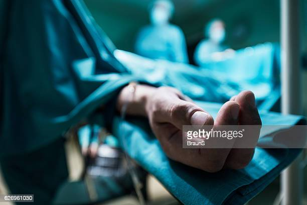 Close up of patient's hand on operating table.