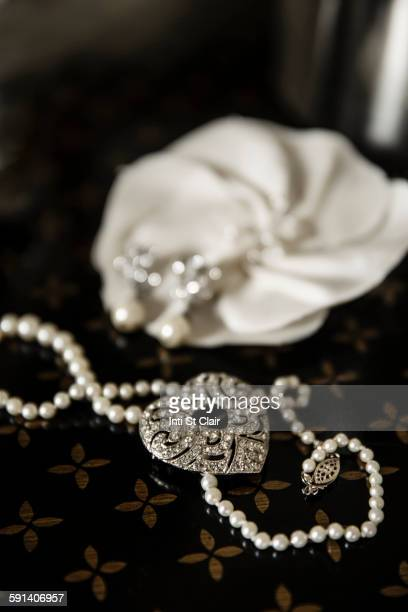 Close up of pearl and heart necklace on table