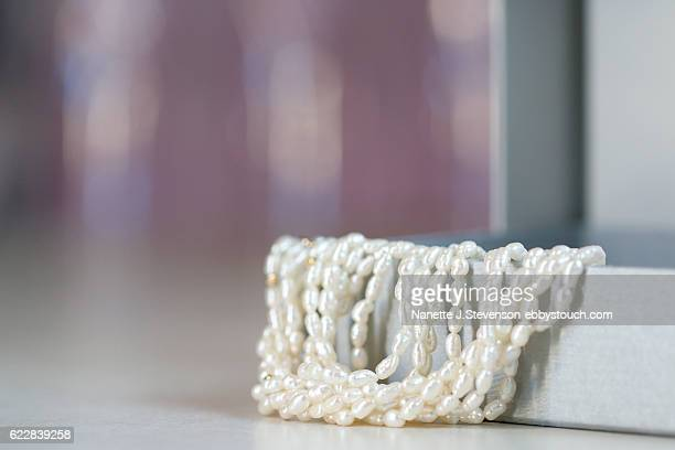 close up of pearl necklace on tabletop - nanette j stevenson stock photos and pictures