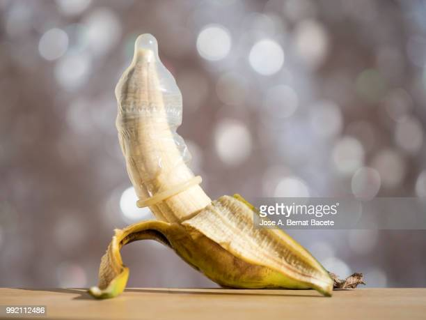 close up of peeled banana  wearing a condom illuminated by the light of the sun. - geschlechtskrankheit stock-fotos und bilder