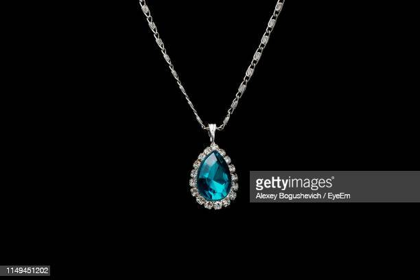 close up of pendant necklace against black background - diamond gemstone stock pictures, royalty-free photos & images