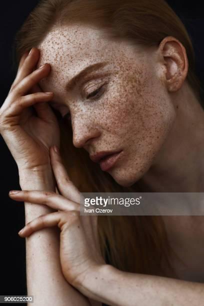 close up of pensive caucasian woman with freckles - sproet stockfoto's en -beelden