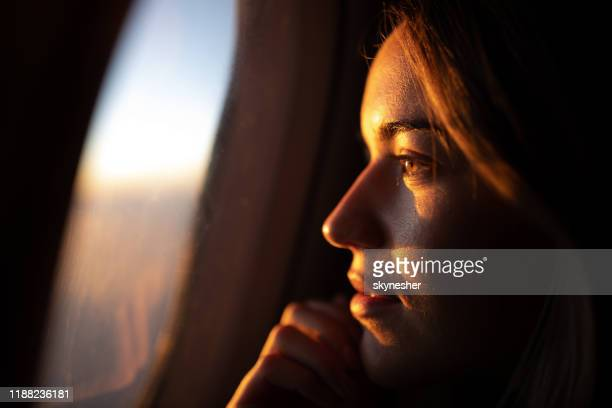 close up of pensive woman looking at sunset through airplane window. - window stock pictures, royalty-free photos & images