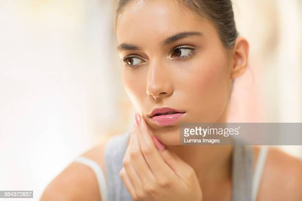 Close up of pensive woman touching cheek