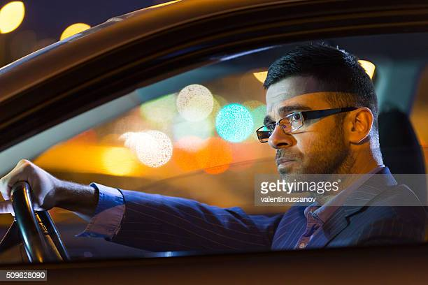 Close up of pensive young man driving his car