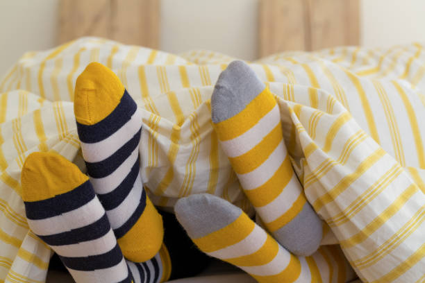 close up of people lying in bed - bedroom socks stock pictures, royalty-free photos & images
