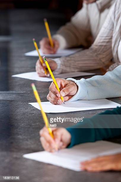 close up of people writing with pencils - college application stock photos and pictures