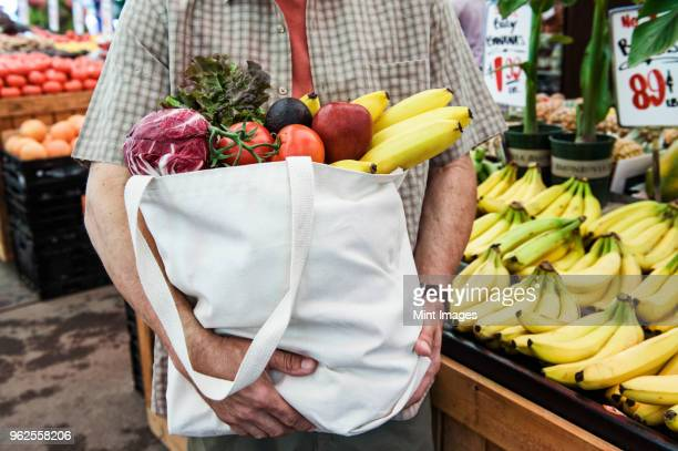 close up of person at a food and vegetable market, holding shopping bag with fresh produce including bananas, tomatoes and cabbage. - local produce stock pictures, royalty-free photos & images