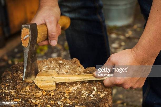 Close up of person holding a hand axe, cutting and shaping a small piece of wood on a splitting block covered in wood shavings.
