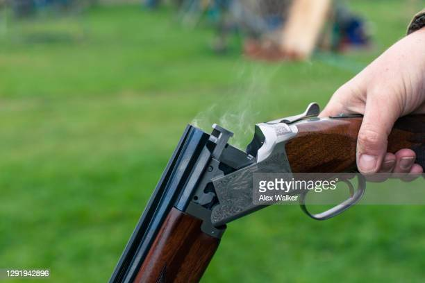 close up of person holding a shotgun with smoke - gunman stock pictures, royalty-free photos & images