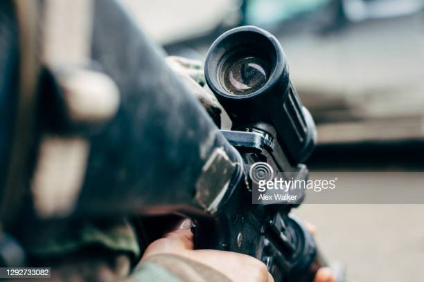 close up of person holding an assault rifle - gunman stock pictures, royalty-free photos & images