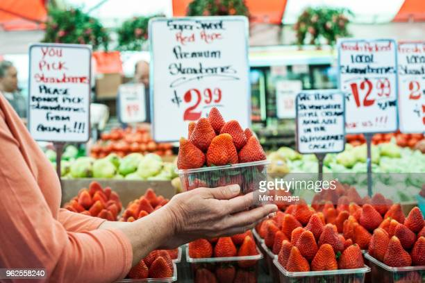 Close up of person holding punnet of fresh strawberries at a fruit and vegetable market.