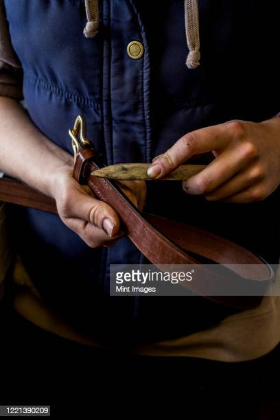 close up of person in saddler's workshop holding leather strap. - strap stock pictures, royalty-free photos & images