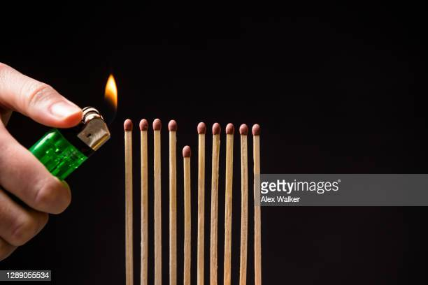 close up of person lighting a line of matchsticks against black background - bad luck stock pictures, royalty-free photos & images